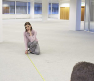 businesswoman with colleague measuring usable area of new office space